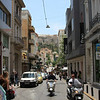 Athens - a busy street scene, with the Acropolis in the background.