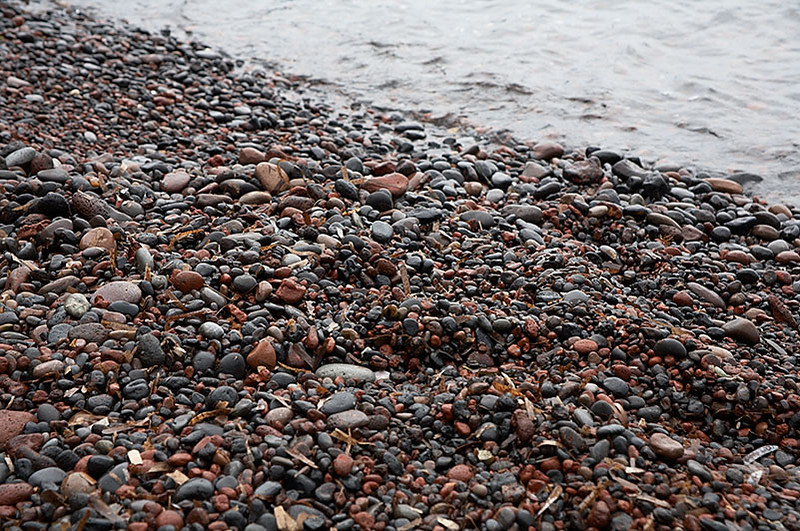 The stones that make up the beach.