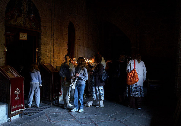 Visitors light candles outside of the chapel.