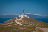 The old lighthouse in the north of Mykonos with the island of Tinos in the background