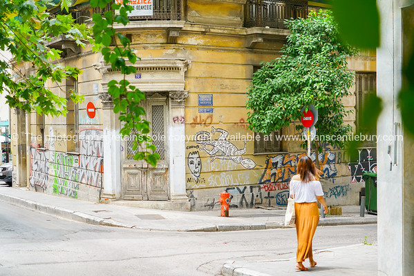 Woman on corner footpathe in orange skirt with graffiti covered old building background.