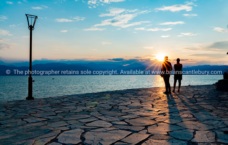 Silhouettes of couple standing looking into sun across sea.