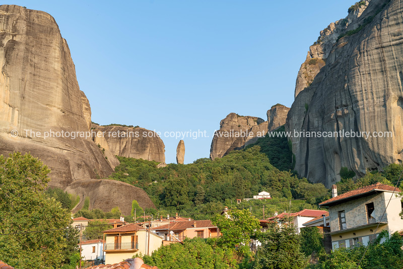 Houses and church in foothills among trees below towering rocks and pinnacles at Meteora.