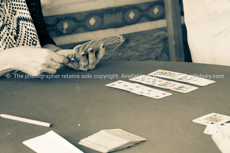 Sepia toned aged image effect  of hand holding the cards playing card during day in Greek hill village bar.