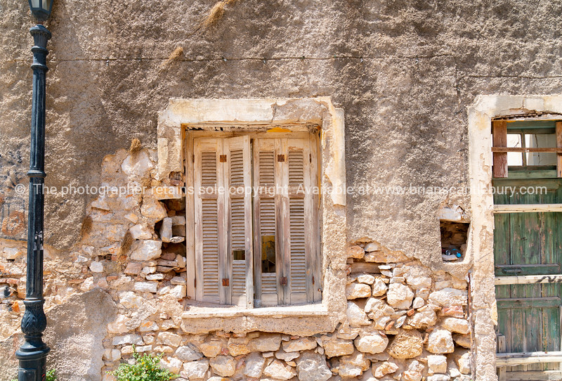 Old deteriorating stone wall with closed wooden shutters