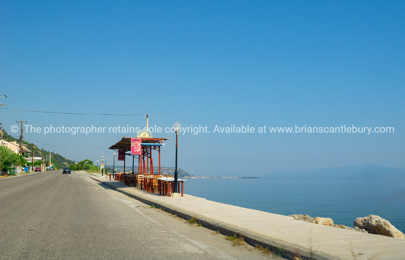 Restaurant tables and chairs set up on footpath along seaside and between sea and highway.