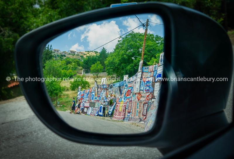 Roadside display of Greek rugs for sale