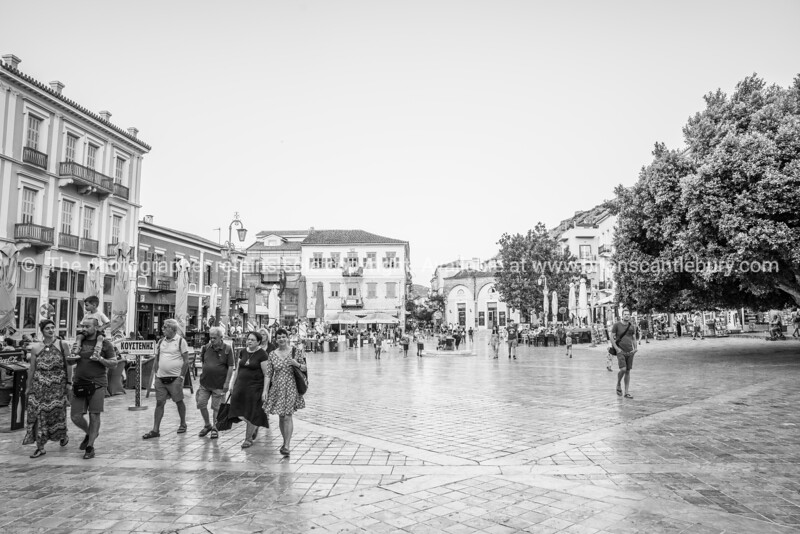 People moving around in town square in small  Greek village