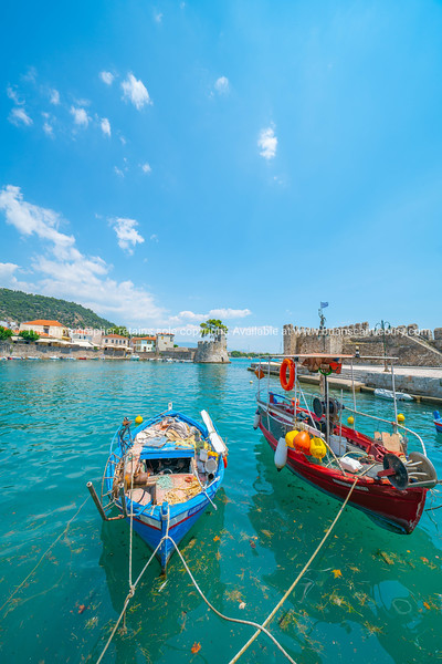 Two fishing boats moored at pier with entrance to fortified medieval harbour behind.