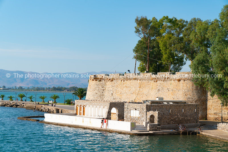 Rock retaining wall and historic fortification with path around coastline at Nafplio.