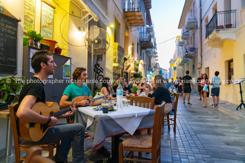 Diners on the city street entertained by duo singing Greek songs