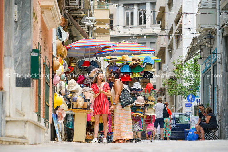 Two women enjoy conversing in front of street vendors hat stand in Plaka area of city.
