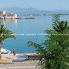 View across promenade to island Bourtzi with old fortress set in blue Mediterranean off-shore from Nafplio.
