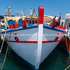 Newly painted white red and blue fishing boat moored at dock