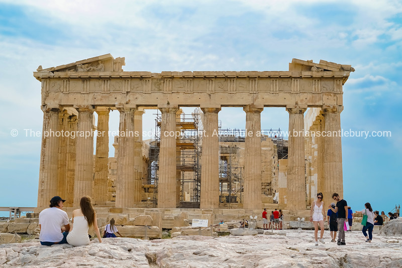 Parthenon Temple on acropolis hill undergoing restoration with saffolding erected inside and tourists walking and relaxing on rock area around structure.