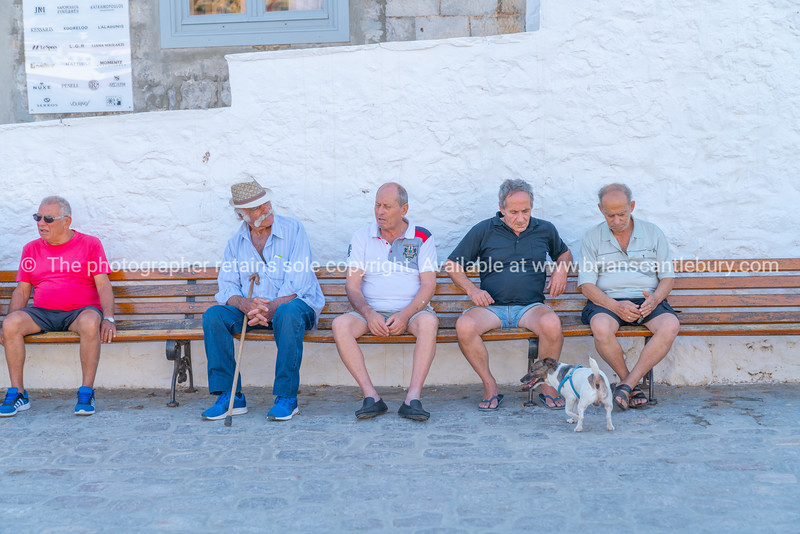 Greek men in their daily ritual gathering to sit and talk in town