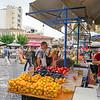Street fruit vendor weighs bag of fruit for customes in Plaka