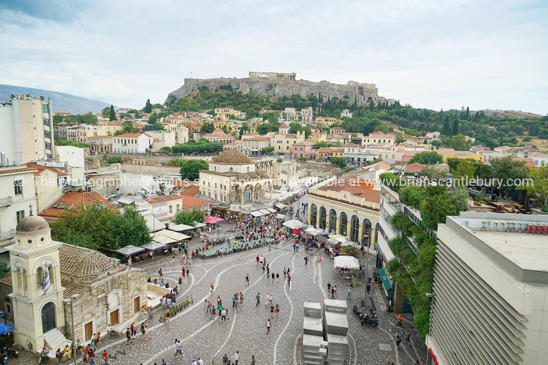 People wander through Plaka square past souvenir, trinket and food vendors surrounded by buildings and in view of acropolis on hill behind.