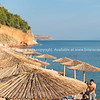 Sun shade umbrellas lined up along waters edge in summer for beach goers and holiday makers to relax under.