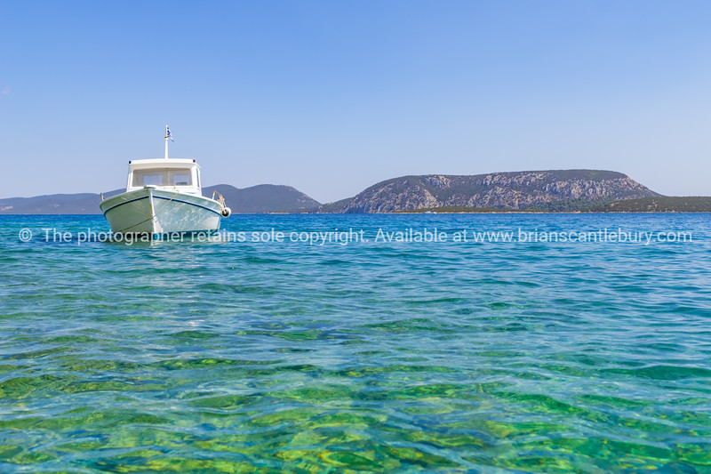 traditional style boat afloat and moored in blue Mediterranean off Peloponnese coast.