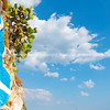 Rock retaining wall and around coastline at Nafplio with Greek flag and prickly pear cactus against blue sky