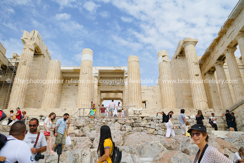 Crowd of tourists clambering around ancient structures of the acropolis