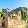Large imposing rocks rise behind quaint Greek stone church