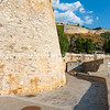 Rock retaining walls and historic fortification with path around coastline at Nafplio.