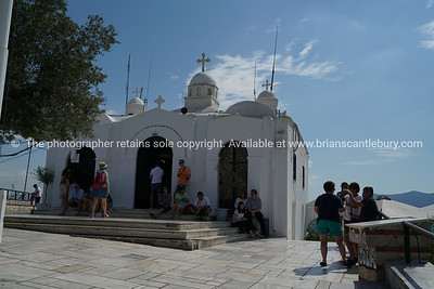 Whitewashed Greek Orthodox Church of Saint George Lycabettus and tourists.