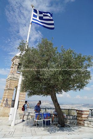 Cold drinks vendor under olive tree, flagpole and belltower at summit Mount Lycabettus