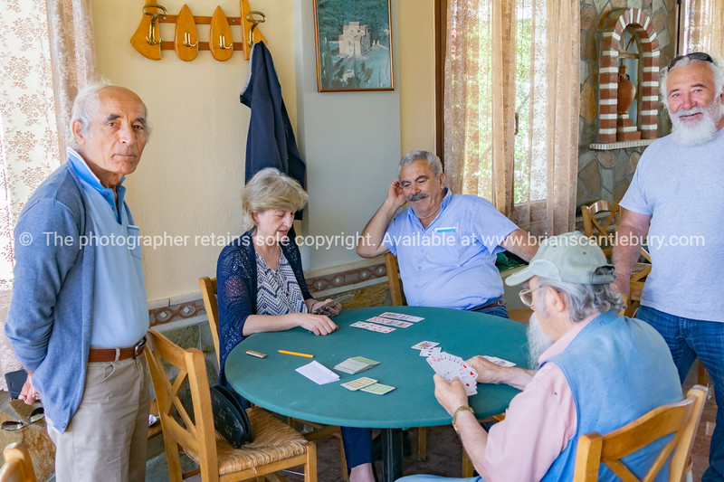 Elderly people playing card during day in Greek hill village bar.