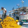 Fisherman checks and mends bright yellow fishing nets on wharf