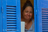 Woman looking out of window, Galissas, Island of Syros, Cyclade Islands, Aegean Sea, Greece