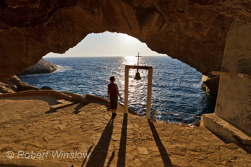 Model Released, Woman by Bell, Cave and Church of Agios Stefanos, Island of Syros, Cyclade Islands, Aegean Sea, Greece