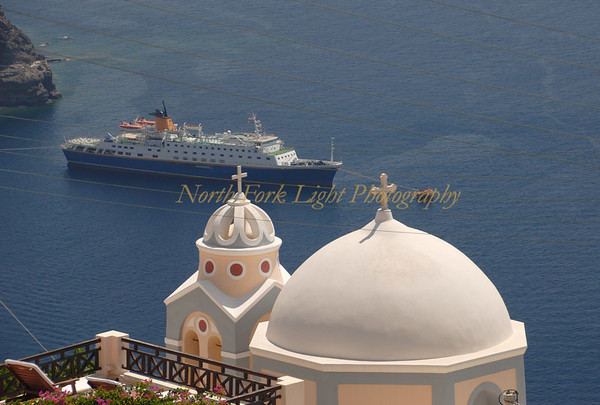 Greek Orthodox church dome overlooking Santorini harbor with cruise ship.