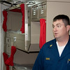 Petty Officer Burke showing the new racks on board the USS Green Bay