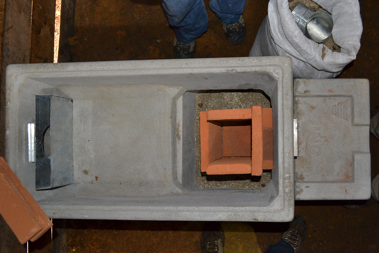next is the installation of two metal inserts and the red clay fire box