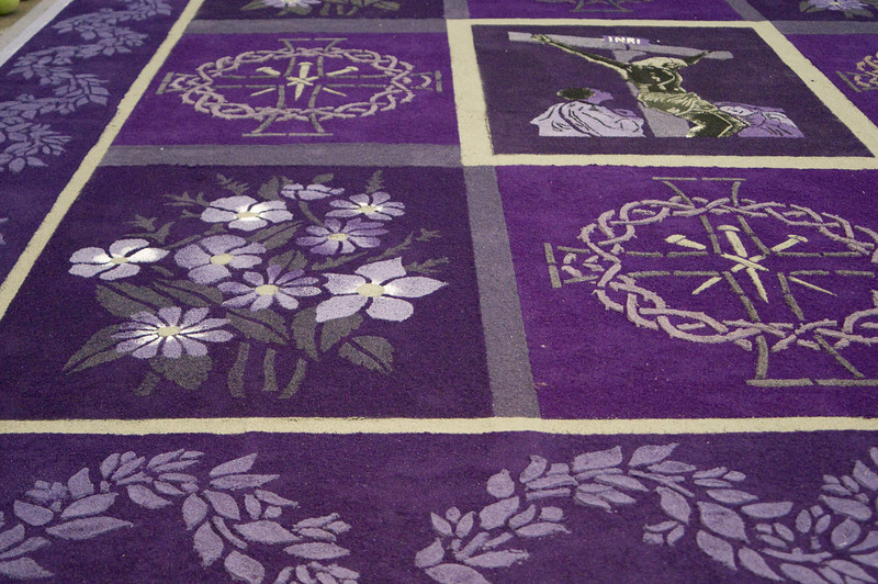 "This is made of saw-dust tinted in different colors. The ""alfombra"" (carpet) is made during lent and it is changed every few days. Also, fruits and vegetebles are placed as offerings around it.<br />  Antigua, Guatemala"