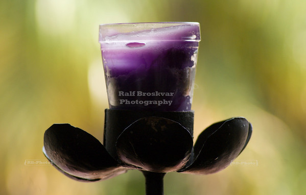 Purple outdoor candle in a glass on an iron flower-shaped candle holder