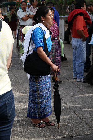 A lady in indigenous garb, with a baby strapped to her back. When the Spanish conquered the Mayans, they assigned each town a special pattern of skirt to wear as a means of population control. Now, the Mayan people still wear those skirts, although they have added to the patterns to tell their story.
