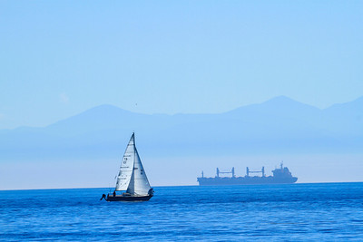 A skiff sails the waters of the Canadian Gulf Islands with a ghost-like freighter in the background.