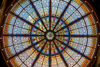 The Tiffany-style stained glass roof soars in the rotunda of the Palm Room at the Empress Hotel in Victoria, BC, Canada. The roof had caved in during a snowstorm in the 1960's and covered over. It was rediscovered while a $45 million remodel of the hotel was taking place in 1989 and restored to its former glory with period glass gathered from all over the world. A whisper is magnified many times over while standing standing directly under the roof, and a normal conversation can be heard by shop keepers quite some distance away.