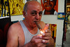 Artist lighting up his cigar in front of his paintings in the outdoor market.