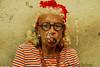Elder woman street performer posing with cigar