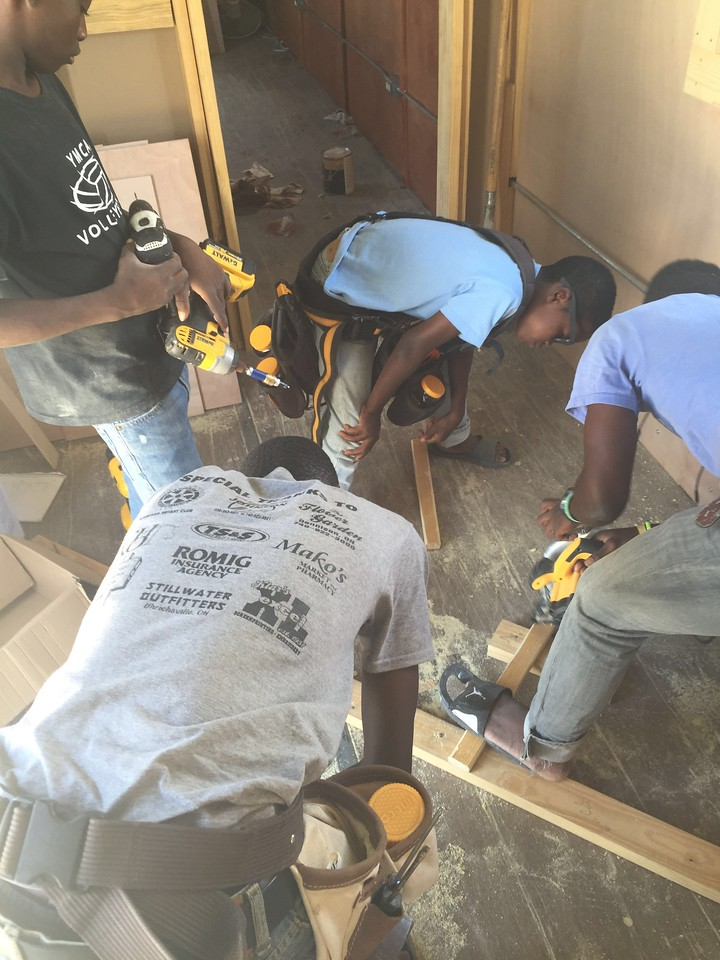 """Day #5<br /> The boys helping work in the office. <br /> Oscar is seen here sporting a UPD D.A.R.E. shirt that somehow made it's way to Haiti. I was floored when I saw him """"report for work"""" in the morning wearing it. <br /> By day #5 I had the boys helping even more & even allow them to help make decisions. One decision they made, confirmed by our team, was to keep Melissa & Pascal from being able to see the inside while work continued. They wanted to surprise them with the finished office."""