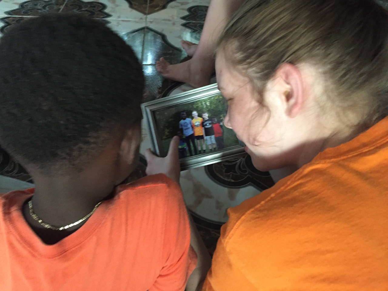 Day #7<br /> Lou-Lou and Hailey relaxing at the team house reviewing a photo of themselves from over the summer when the boys were in Ohio.