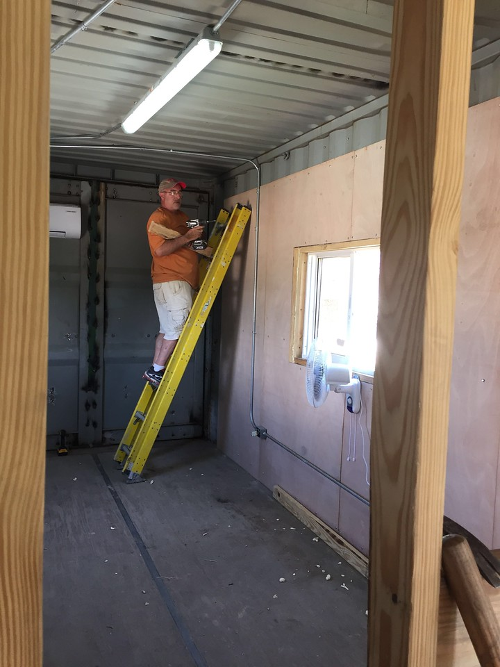 Day#3<br /> It was back to work in the office. Here, Jim is helping pre-drill the plywood panel to be affixed to the inner walls.