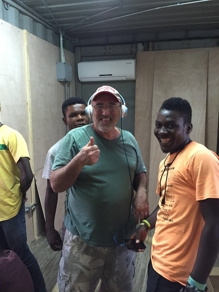 Day #4<br /> Work continues at the office. This photo was taken at around 7pm & we were still working. <br /> Jim took a bit of a break to enjoy some Haitian tunes.