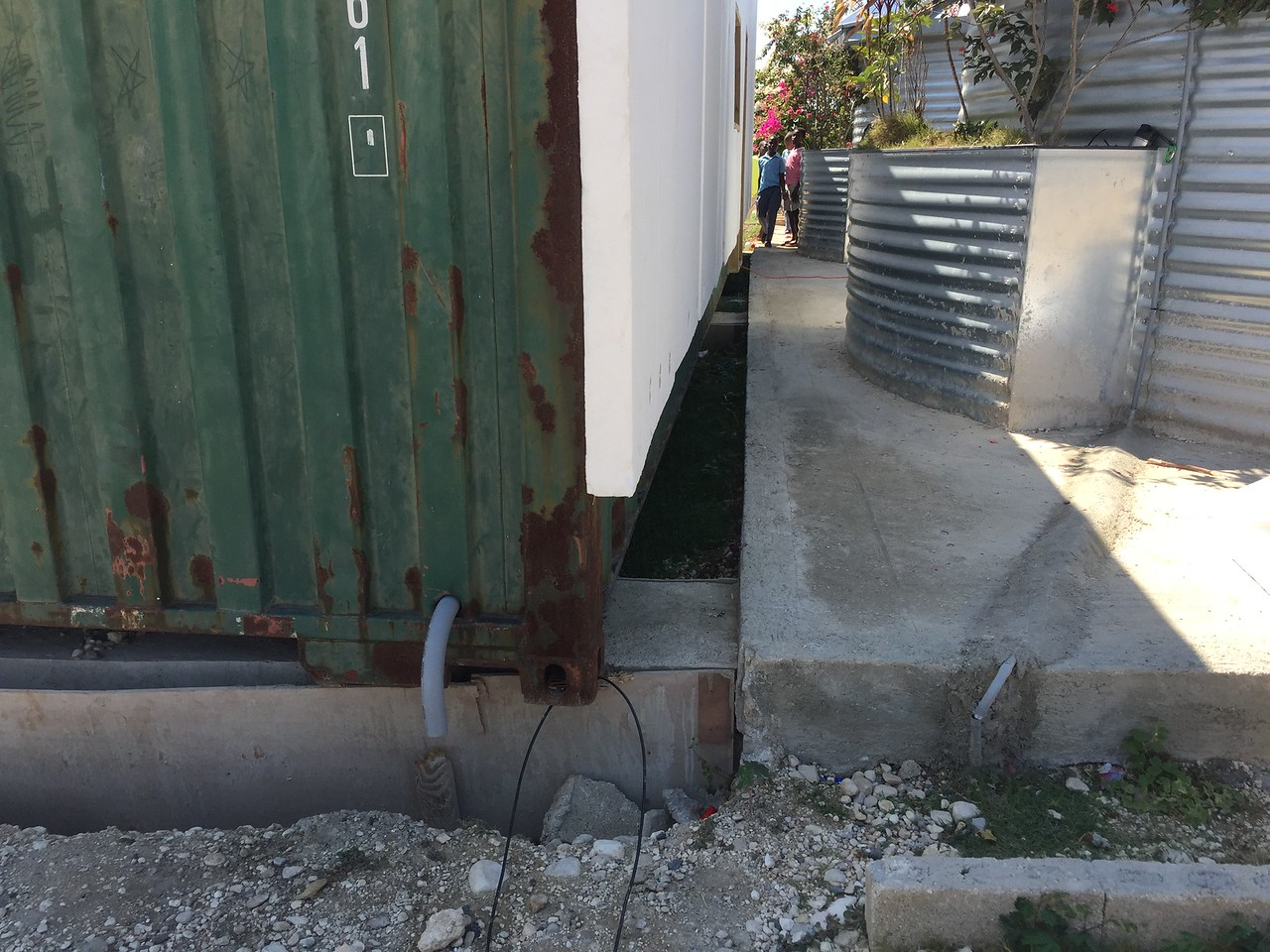 "DAY 4<br /> You can see the concrete pylons previously built. I wanted to shove the container over to close the gap between it, and the concrete slab for the classrooms.<br /> You can also see the ""elbow"" for the power supply going into the container."