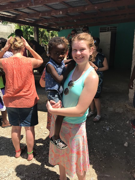 DAY 6<br /> Part of our team visiting Ne-Ne's orphanage.<br /> Hailey with one of Ne-Ne's kids.<br /> <br /> *The roof seen in the background was installed by a Park Christian team back in 2016.<br /> <br /> *Photo credit: